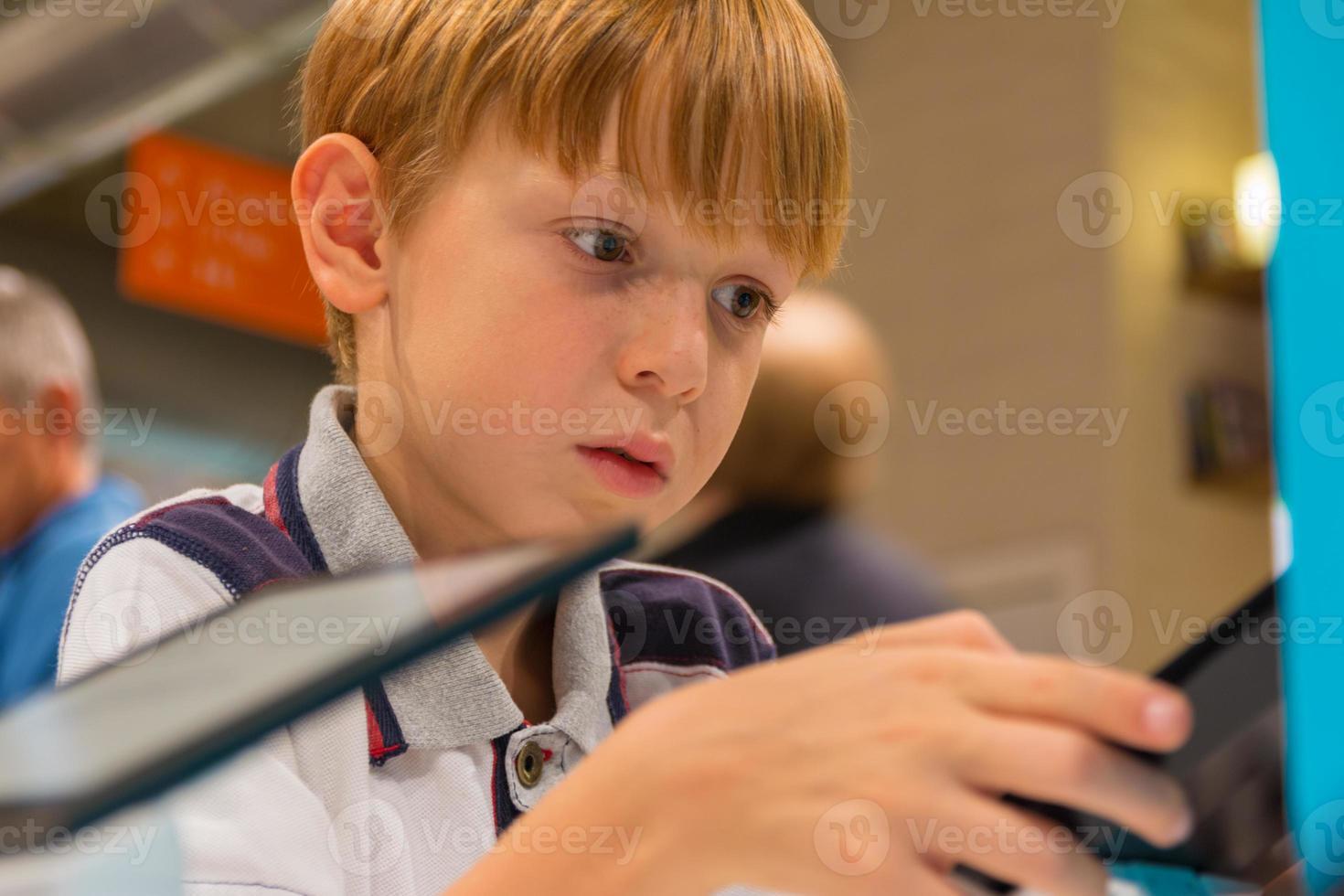 Kind (7-8 Jahre) spielt mit Tablet-Computer in einem Geschäft foto