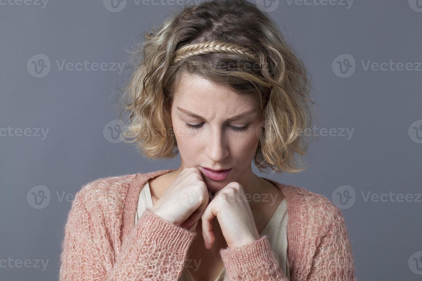 mürrisches junges blondes Mädchen, das schmollt und nach unten schaut foto