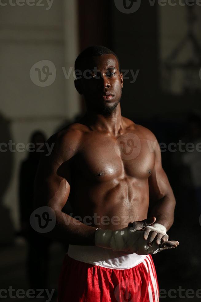 Afroamerikaner männlicher Boxer in roten Shorts im Fitnessstudio foto