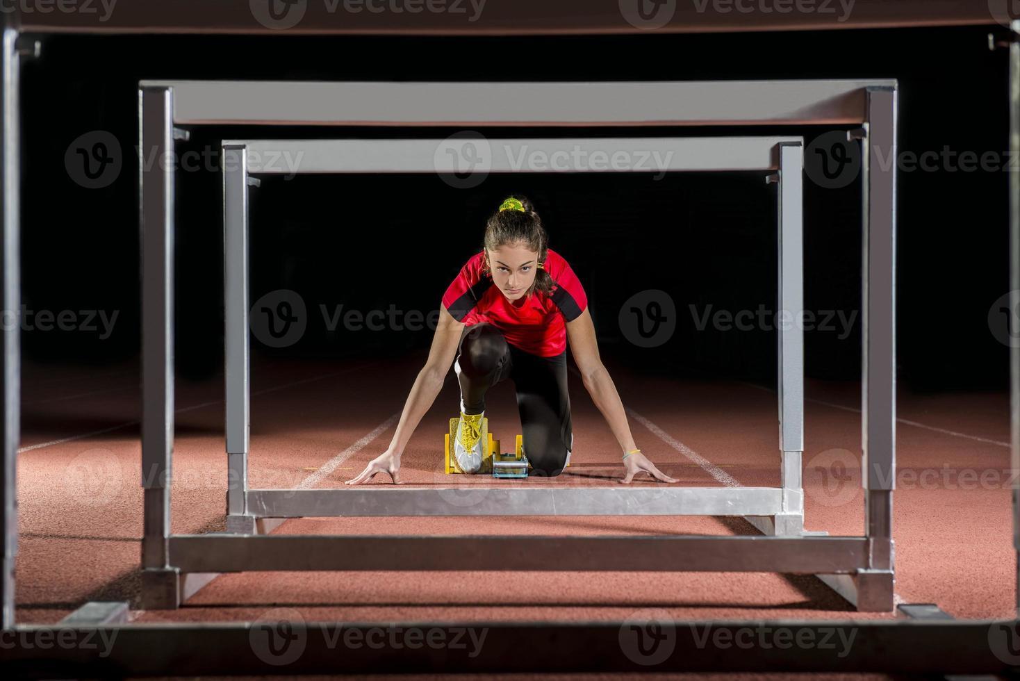 Athlet auf den Startblöcken mit Hürden foto