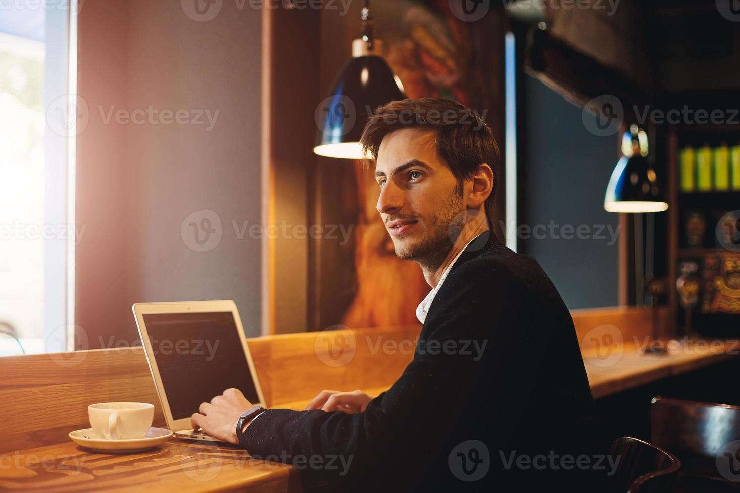 lächelnder Mann, der am Laptop arbeitet, während er mit jemandem plaudert foto