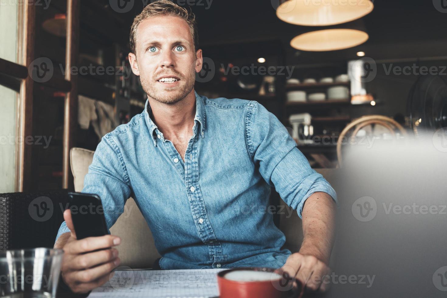junger Unternehmer, der im Café arbeitet foto