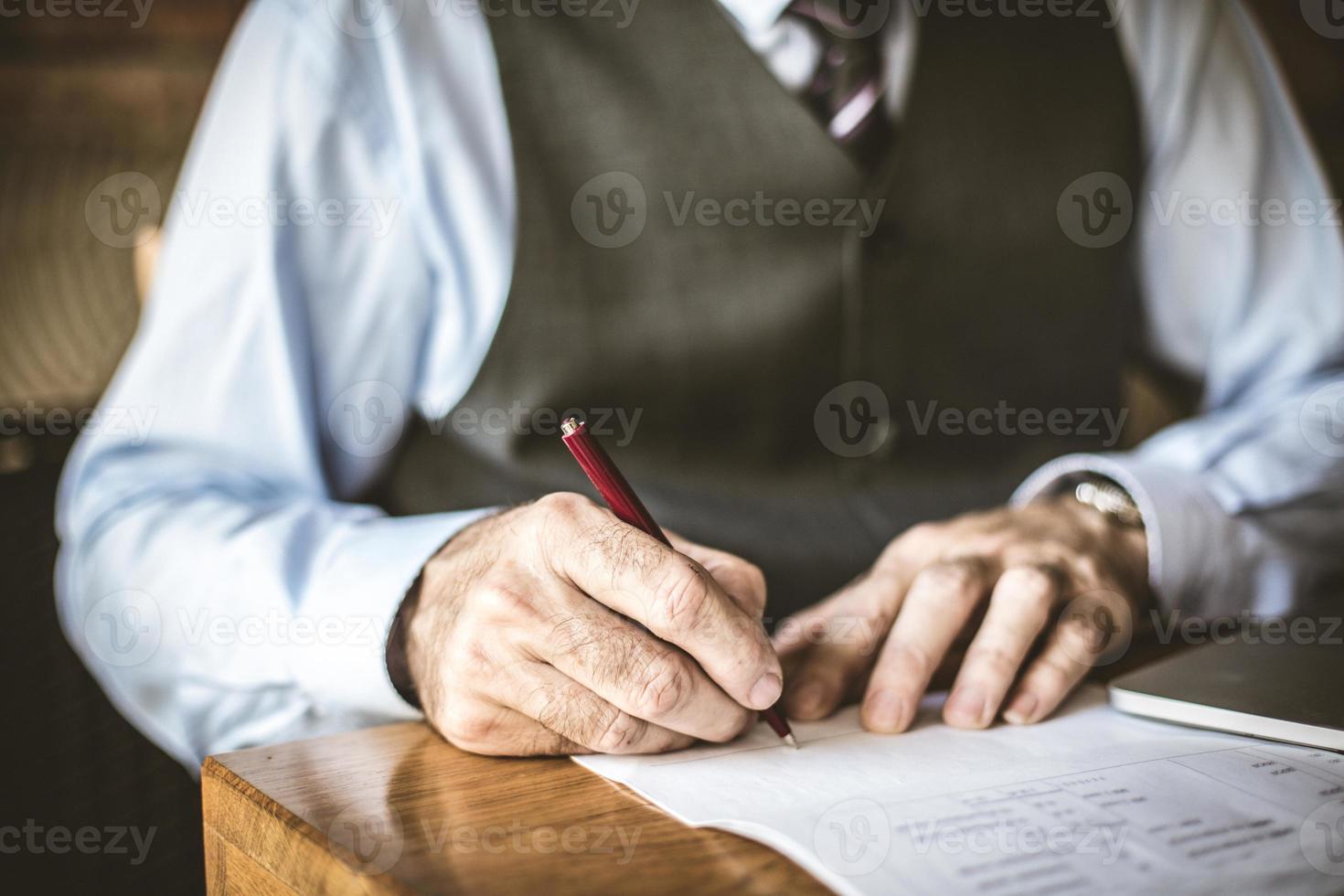 Nahaufnahmebild des älteren Geschäftsmannes unterschreiben in Papieren. foto