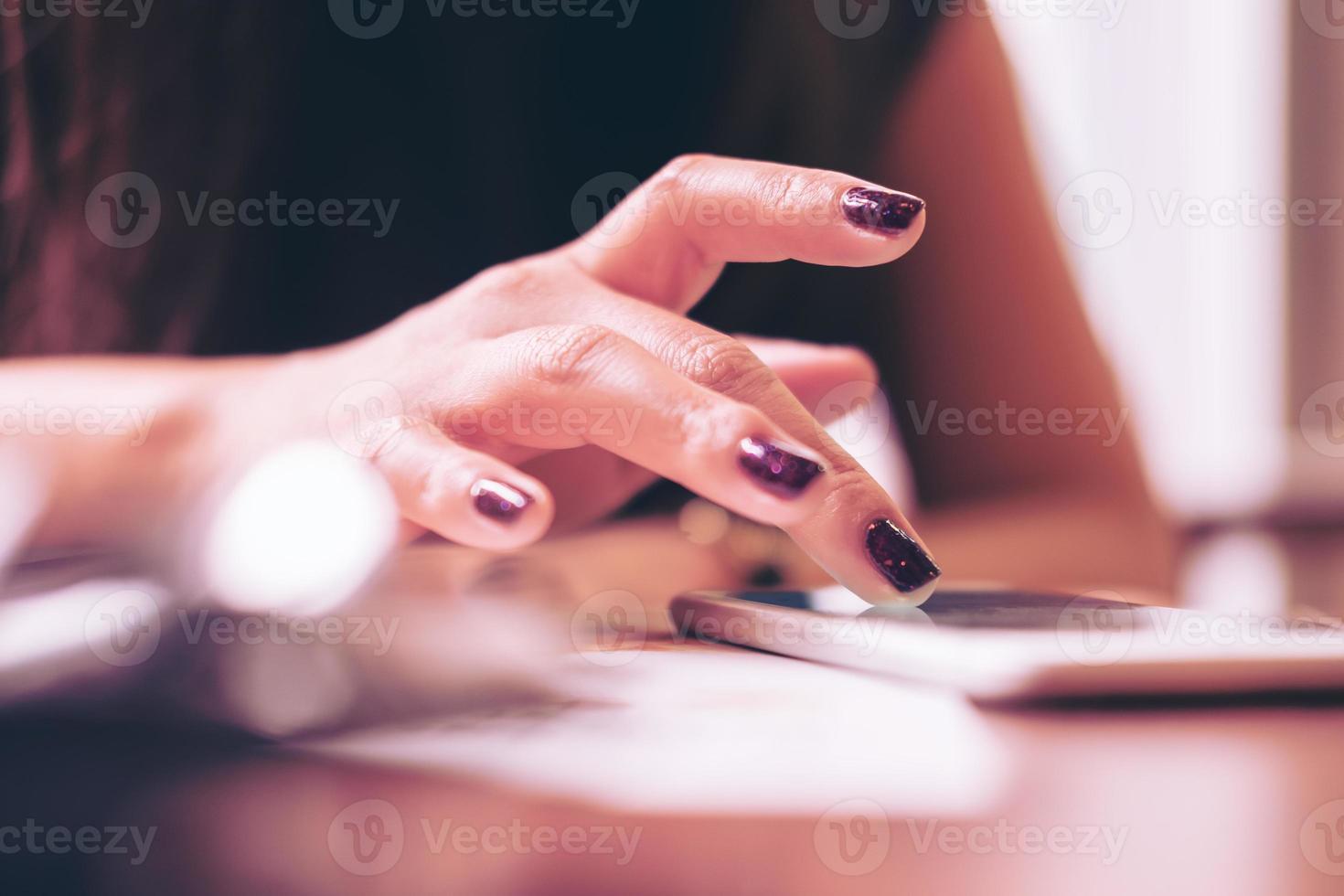 die Hände einer Geschäftsfrau, die Bildschirm des Smartphones auf Holztisch im modernen Café berühren foto