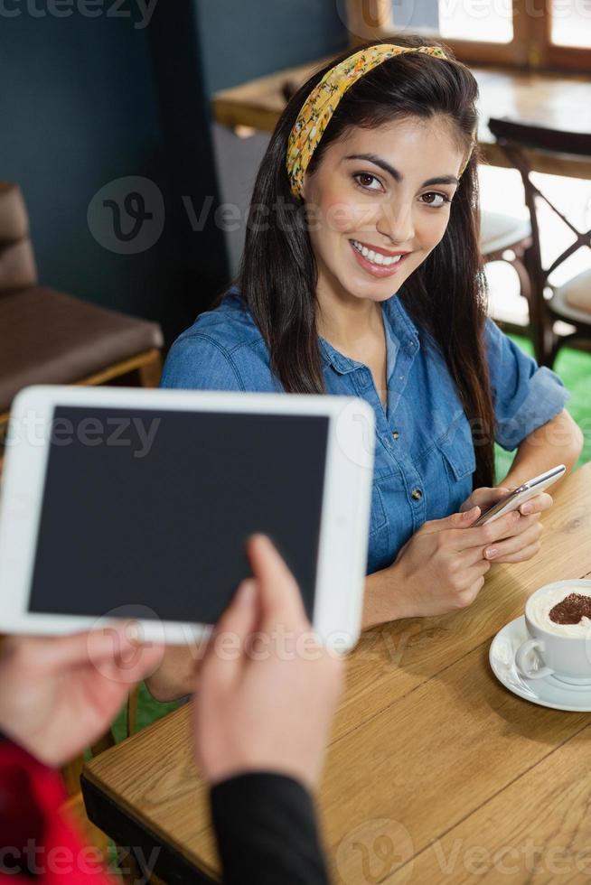 Besitzer hält Tablette, während Frau am Tisch im Café sitzt foto