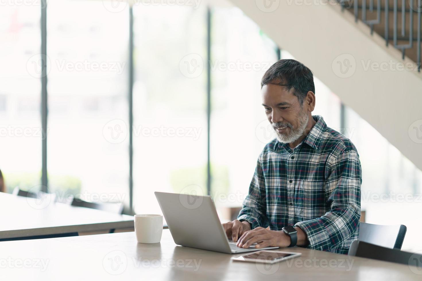 lächelnder attraktiver reifer Mann mit weißem, grauem stilvollem kurzem Bart unter Verwendung des Smartphone-Gadgets, das Internet im modernen Büro, im gemeinsamen Arbeitsraum oder im Café dient. alter Mann mit sozialer Netzwerktechnologie. foto