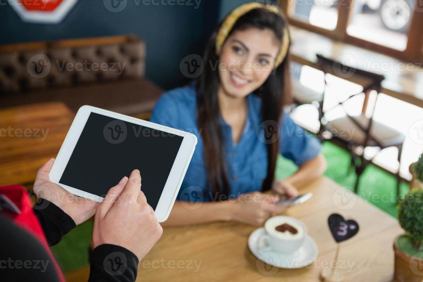 beschnittenes Bild des Besitzers, der Tablette hält, während Kunde am Tisch sitzt foto