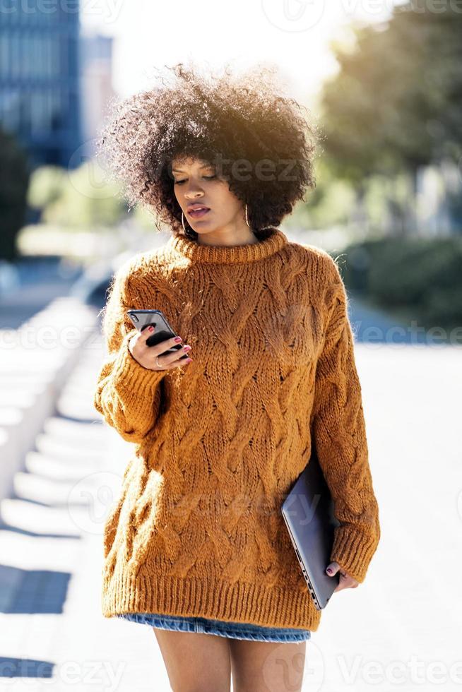 Porträt der attraktiven Afro-Frau mit Handy in der Straße foto