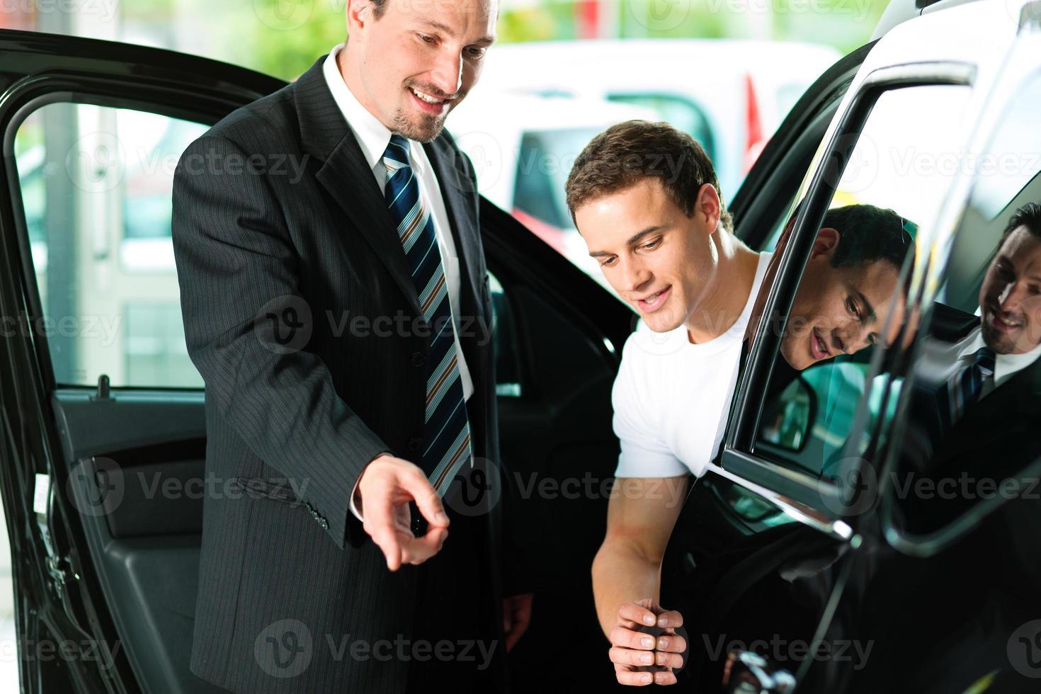Mann kauft Auto vom Verkäufer foto