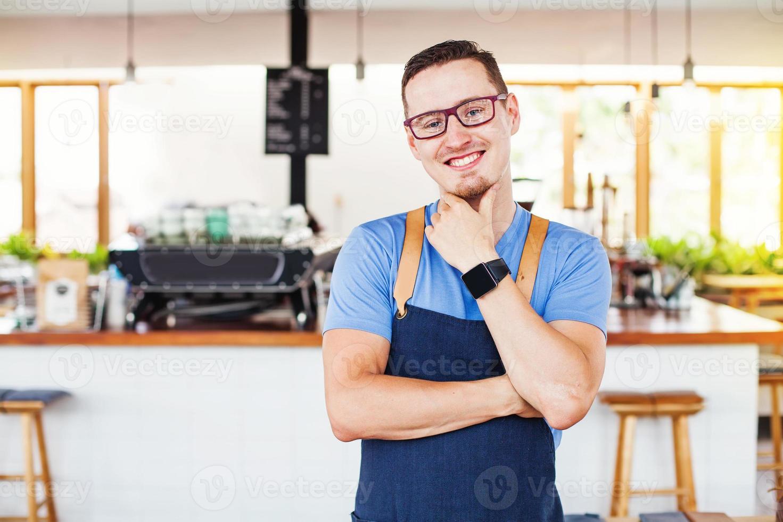 Mann in seinem eigenen Laden, der Kamera betrachtet foto