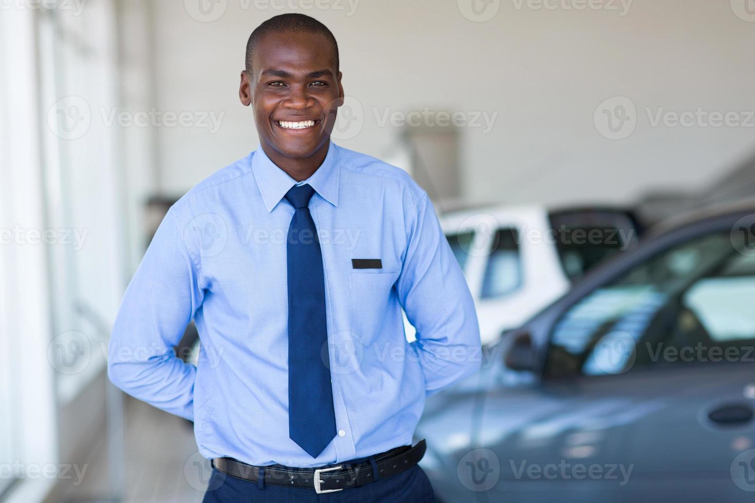afroamerikanischer Verkäufer, der am Fahrzeugausstellungsraum arbeitet foto