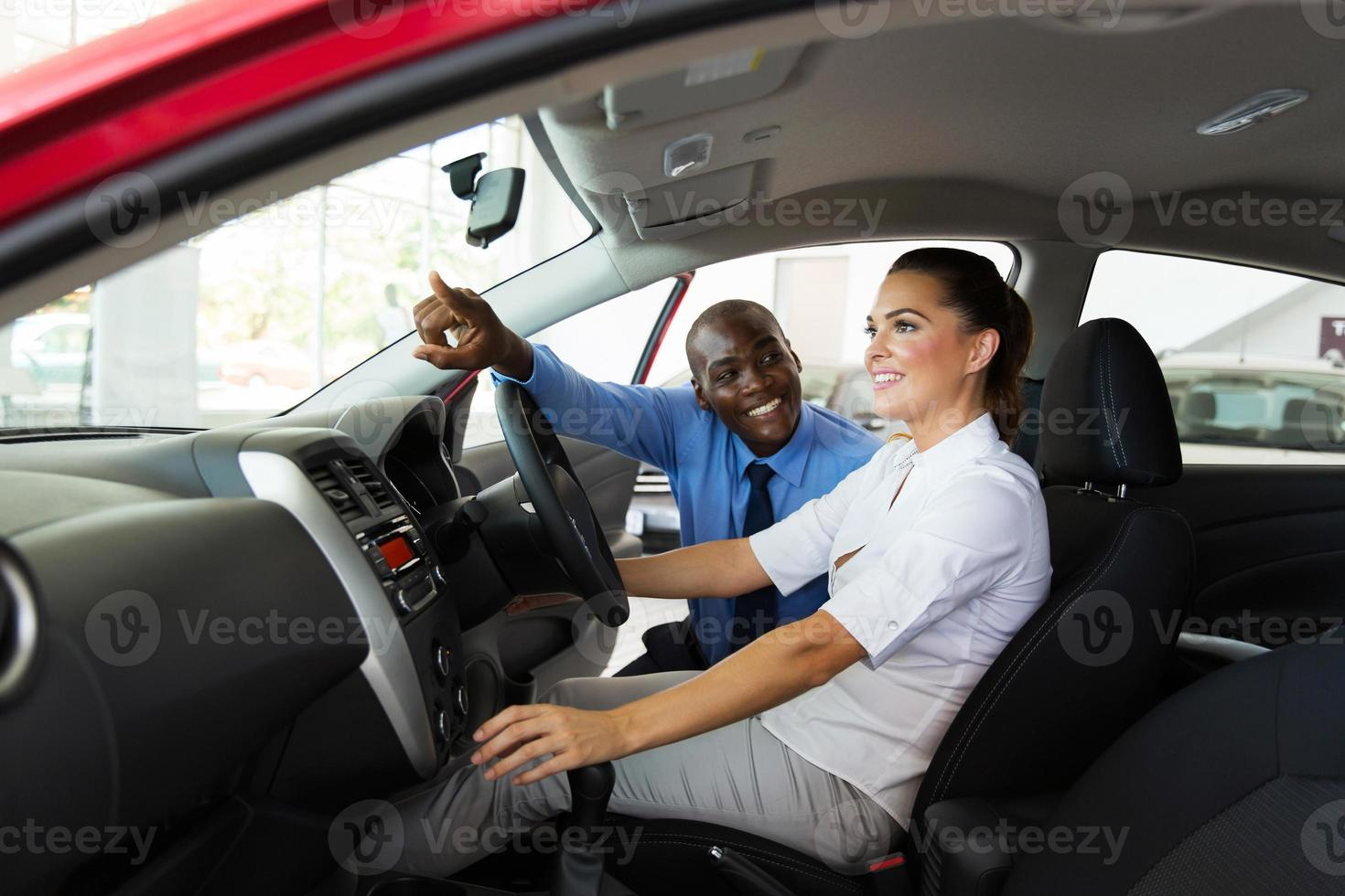 Verkäufer, der jungen Kundin Automerkmale erklärt foto