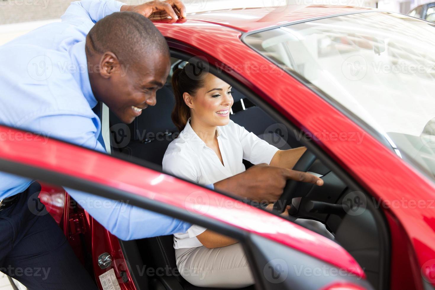 afrikanischer Verkäufer, der der jungen Frau ein neues Auto zeigt foto