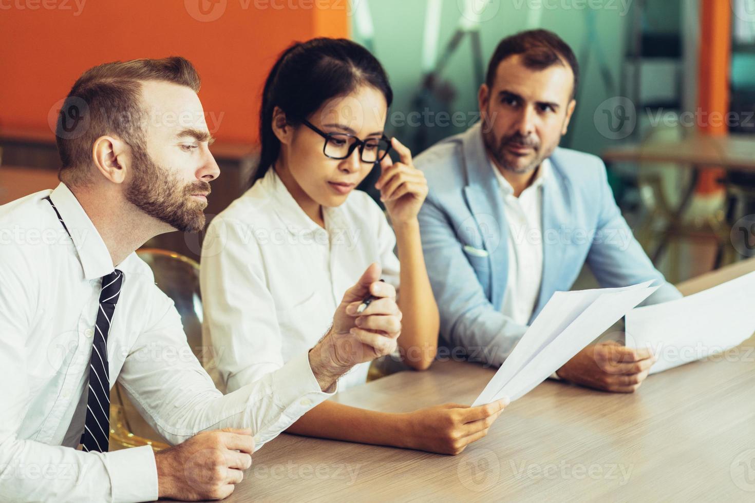 Drei ernsthafte Geschäftsleute lesen und diskutieren Dokumente foto