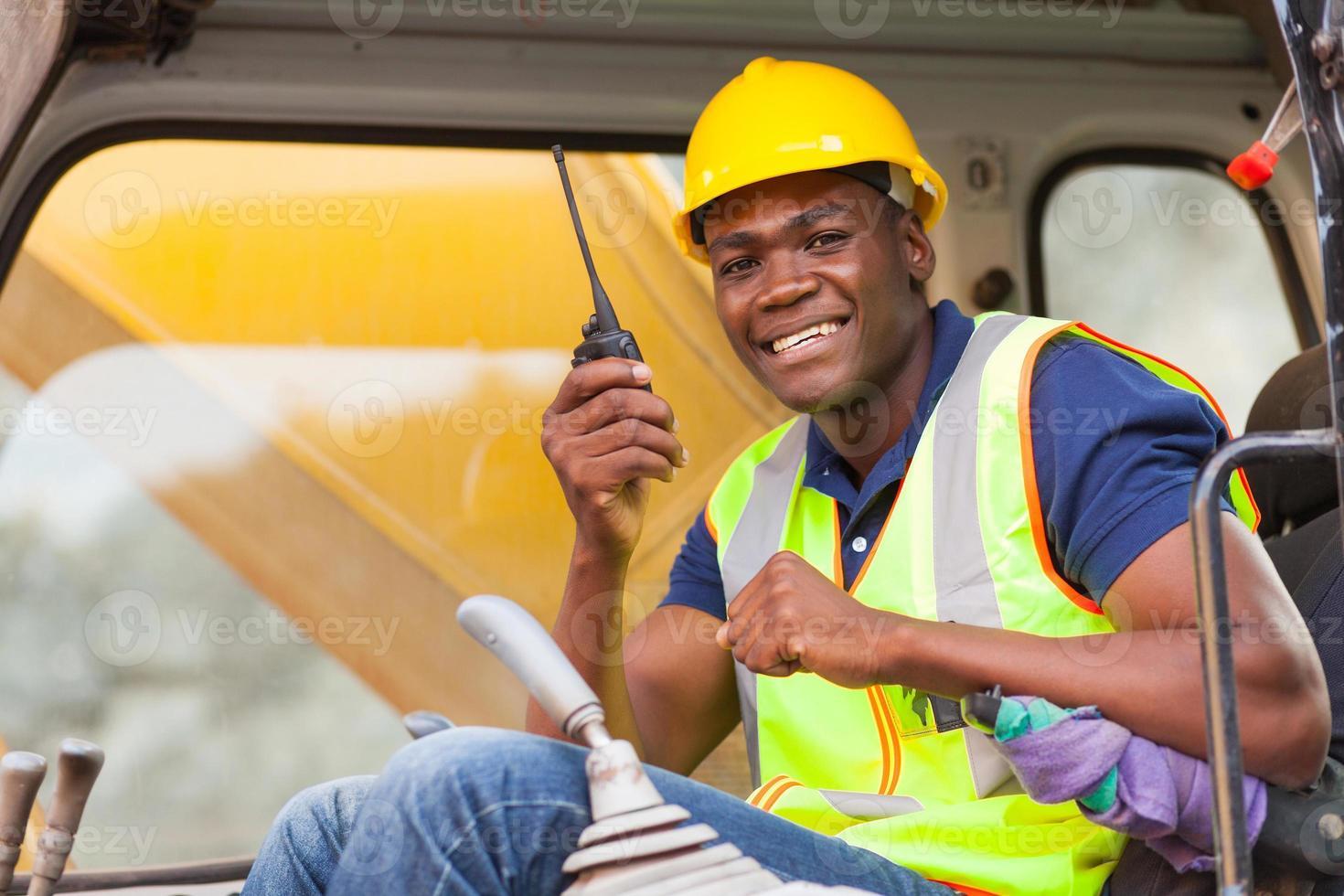 afrikanischer Bulldozer-Betreiber, der auf Walkie-Talkie spricht foto