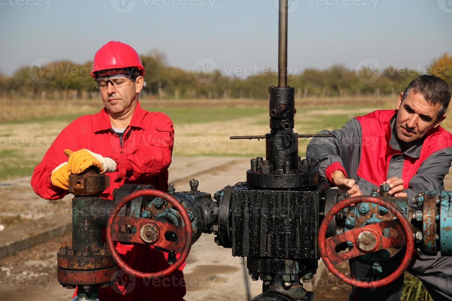 Zwei qualifizierte Öl- und Gasingenieure an der Ölquelle im Einsatz foto