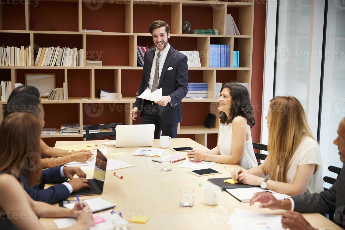 junger männlicher Manager, der an einer Geschäftsvorstandssitzung steht foto