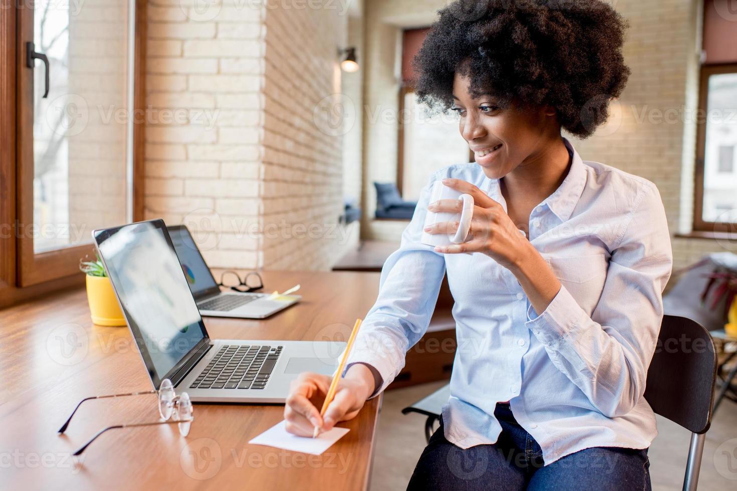 Geschäftsfrau mit Kaffeetasse im Büro foto