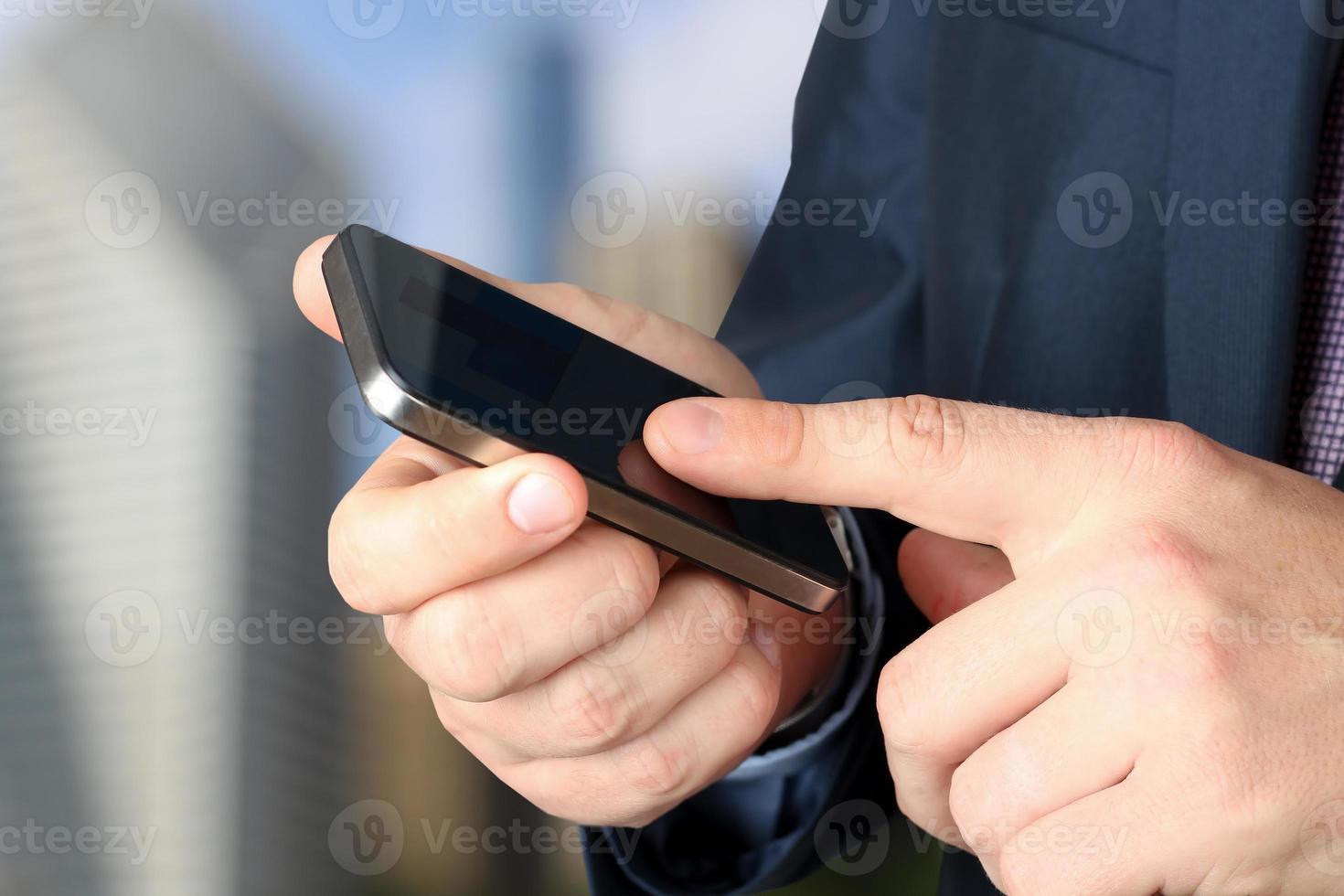 Geschäftsmann, der das mobile Smartphone hält und benutzt foto