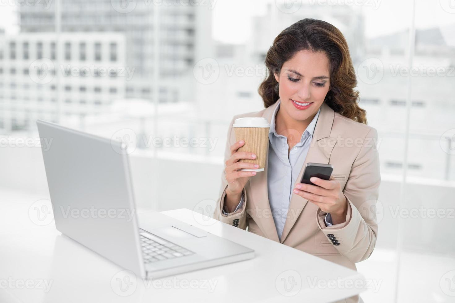 lächelnde Geschäftsfrau, die Einwegbecher und Smartphone hält foto