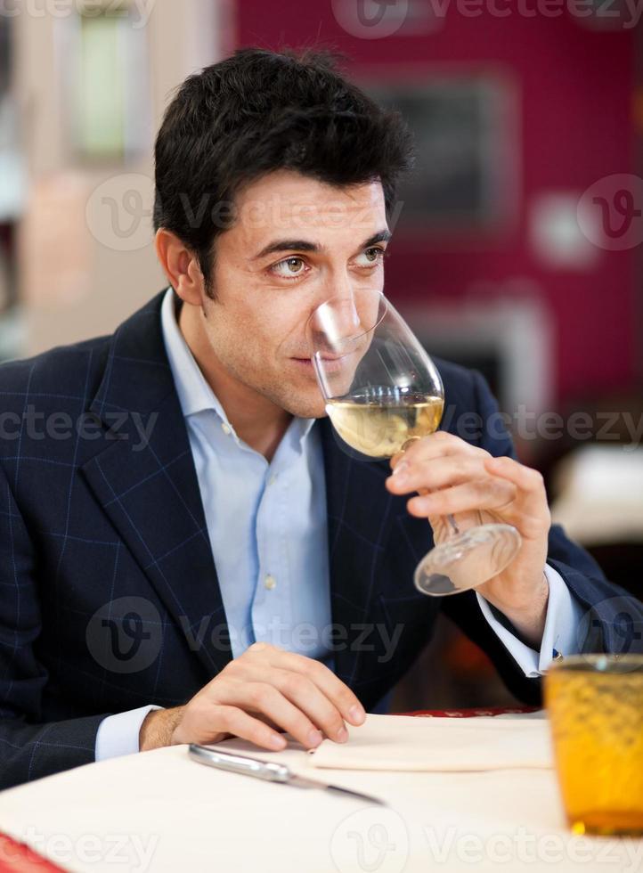 gutaussehender Mann, der ein Glas Wein trinkt foto