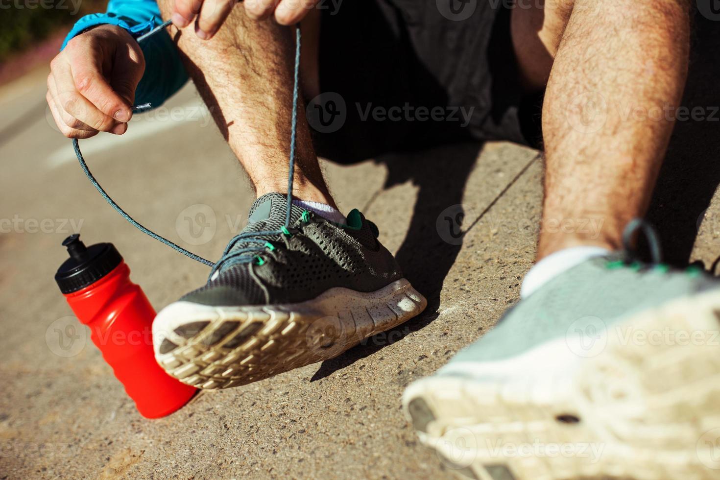 Sportler binden Schnürsenkel an seinen Laufschuhen im Park foto