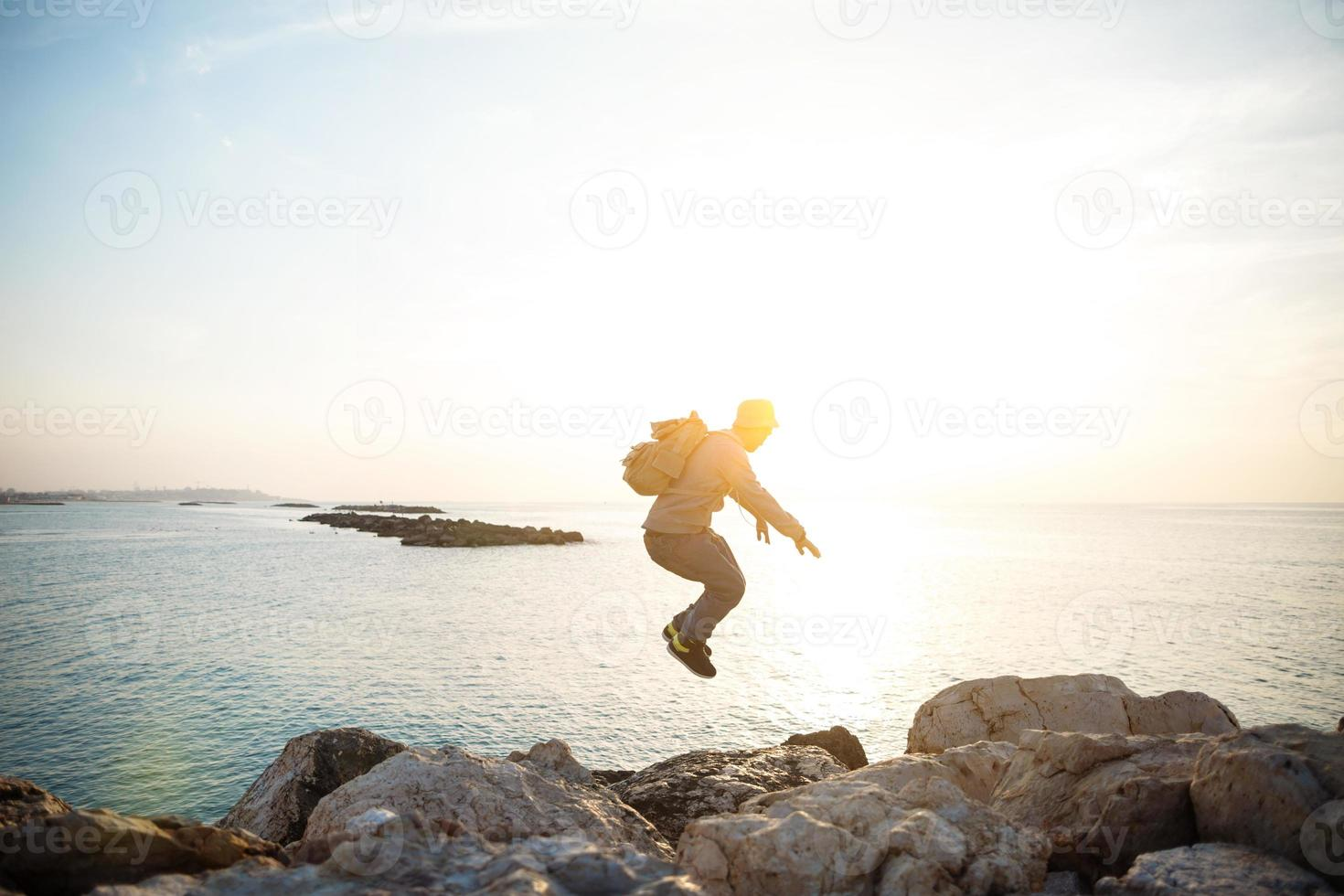 Reisender, der über Felsen nahe dem Meer springt foto
