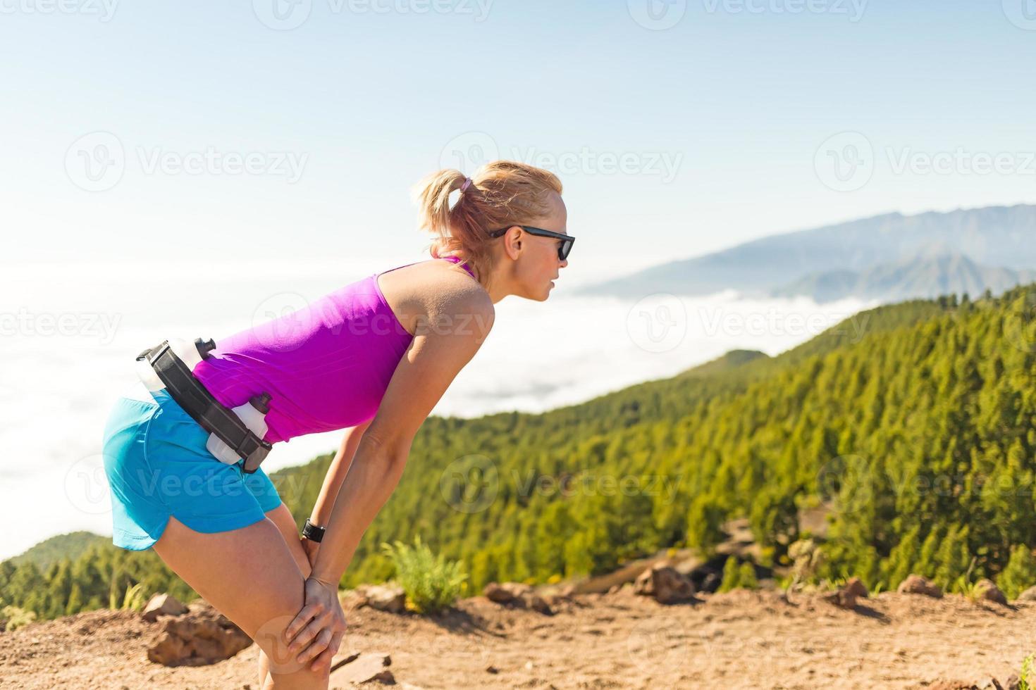 junge Frau holt in den Bergen Luft foto