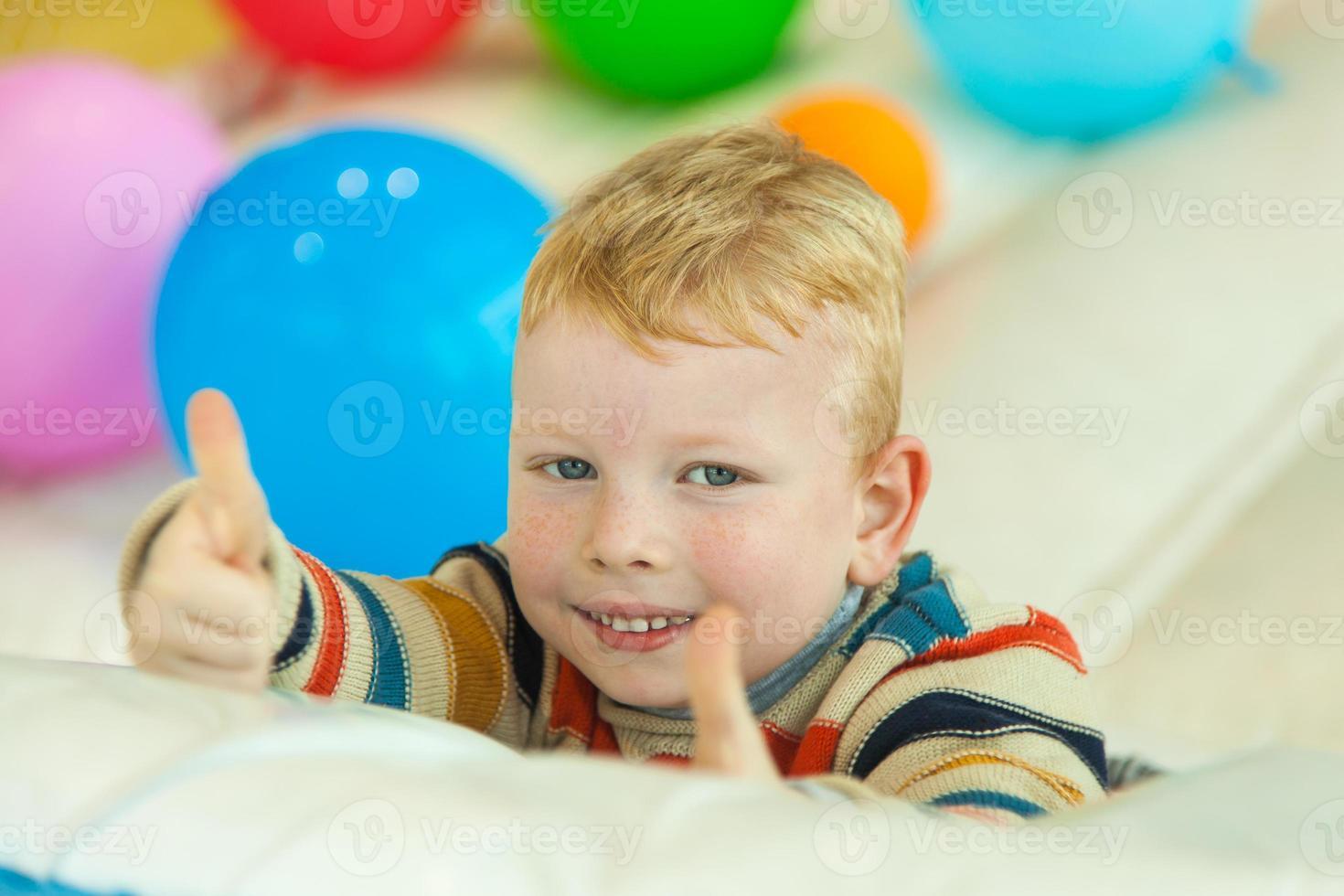 kleiner Junge, der auf dem Boden liegt, umgeben von bunten Luftballons foto