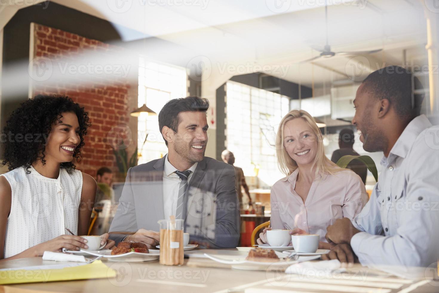 Geschäftsleute, die sich im Café treffen, schossen durch Fenster foto