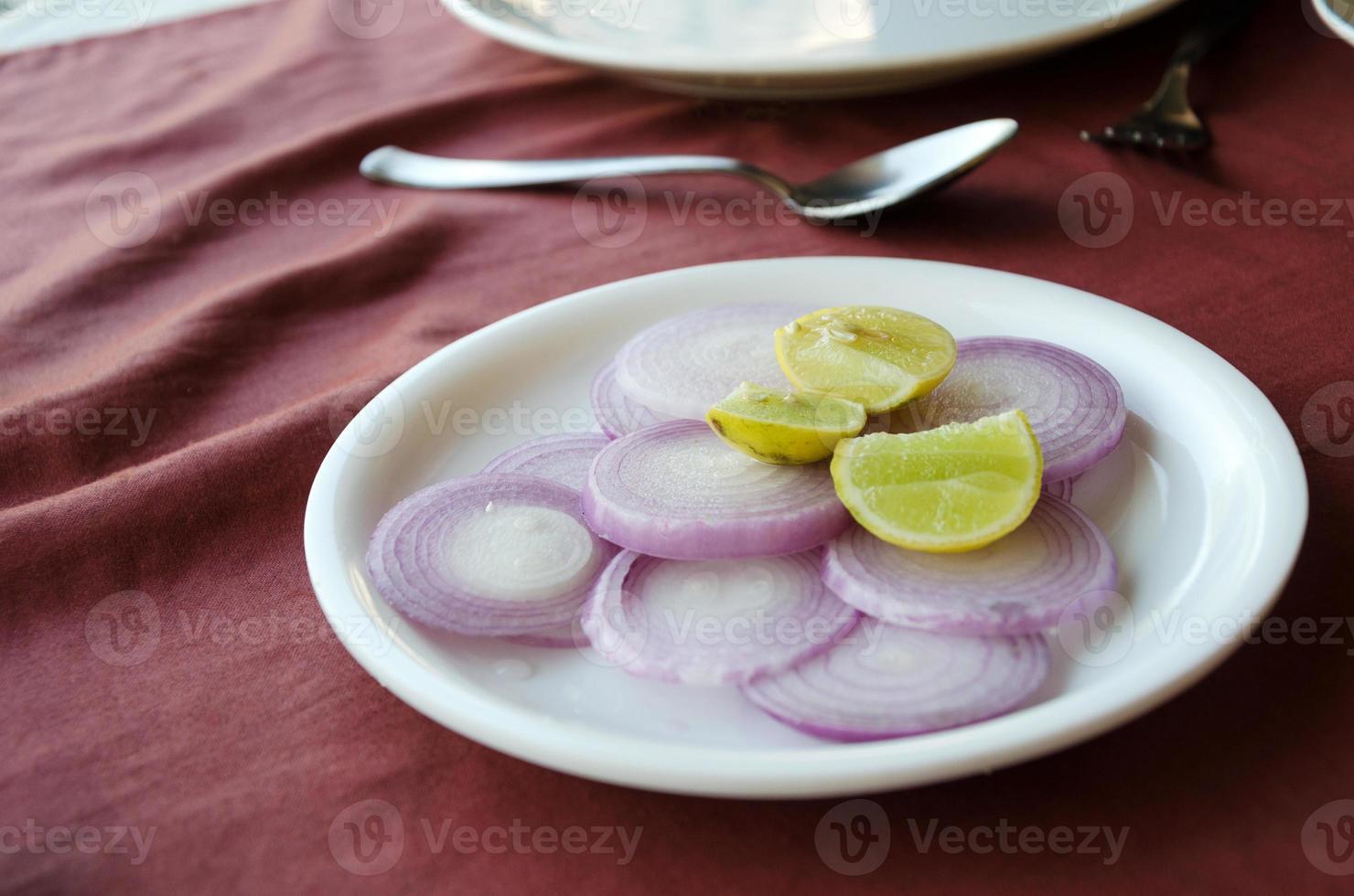 Zitrone und Zwiebeln auf dem Tisch foto