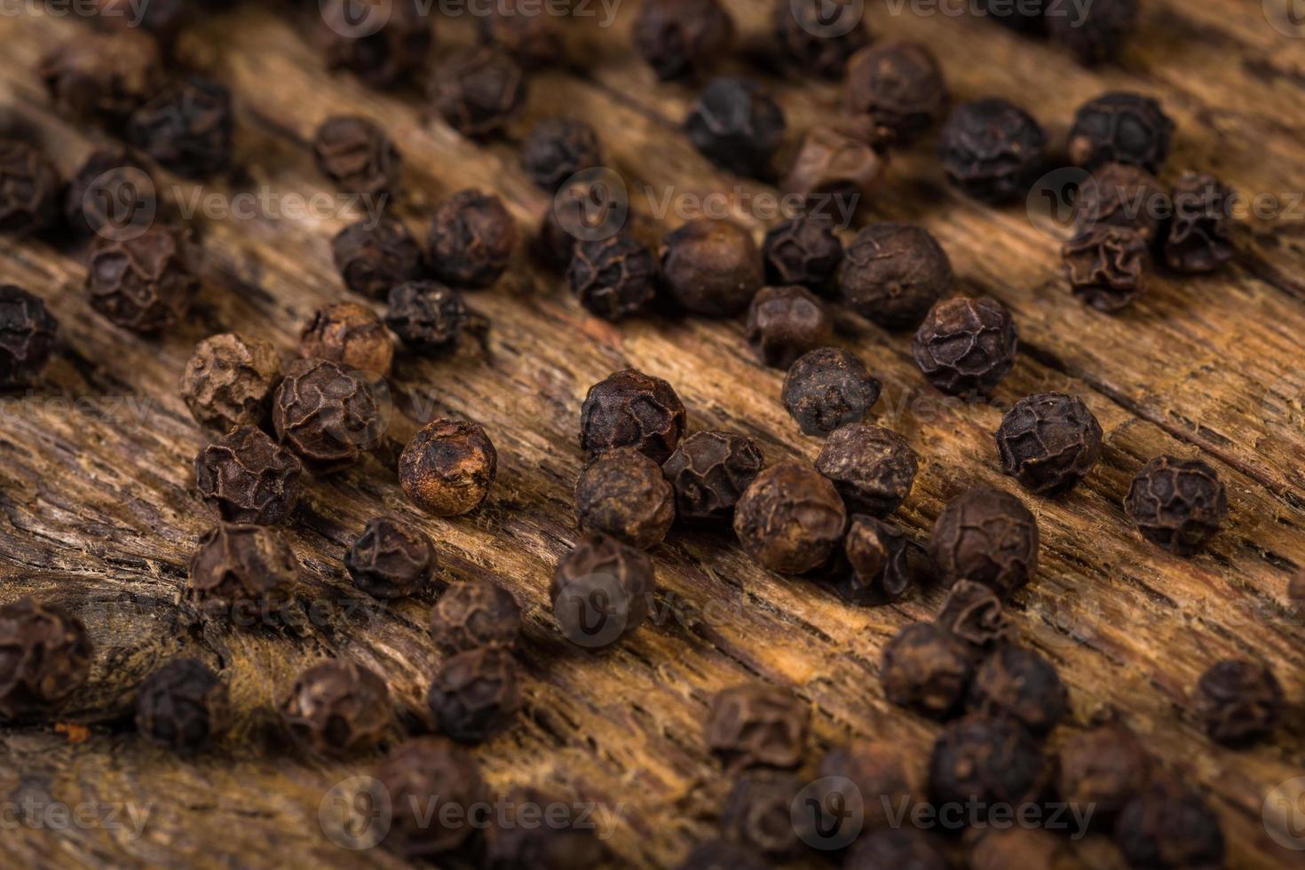 schwarzer Pfeffer auf Holztisch foto