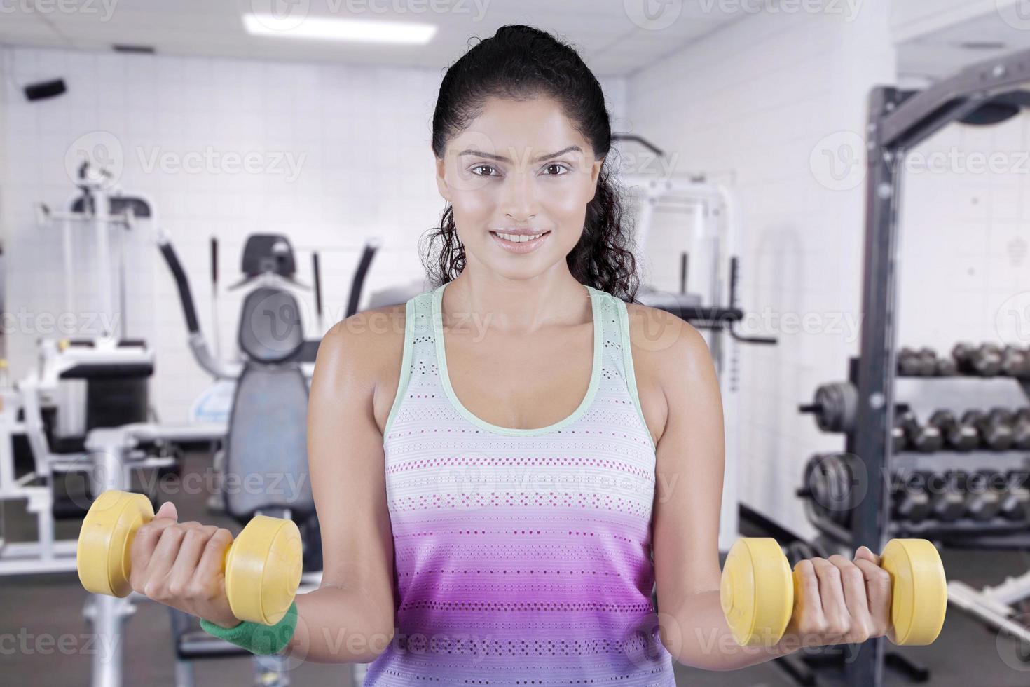 Frau, die zwei Hanteln am Fitnesscenter anhebt foto