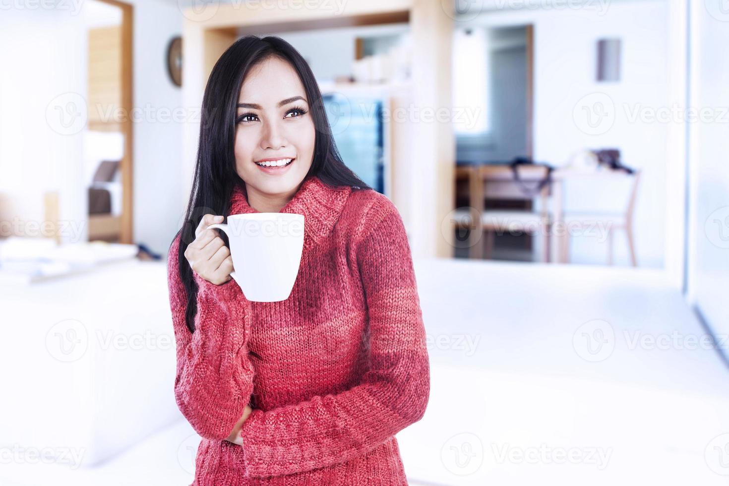 lächelnde Winterfrau, die heißen Kaffee hält foto