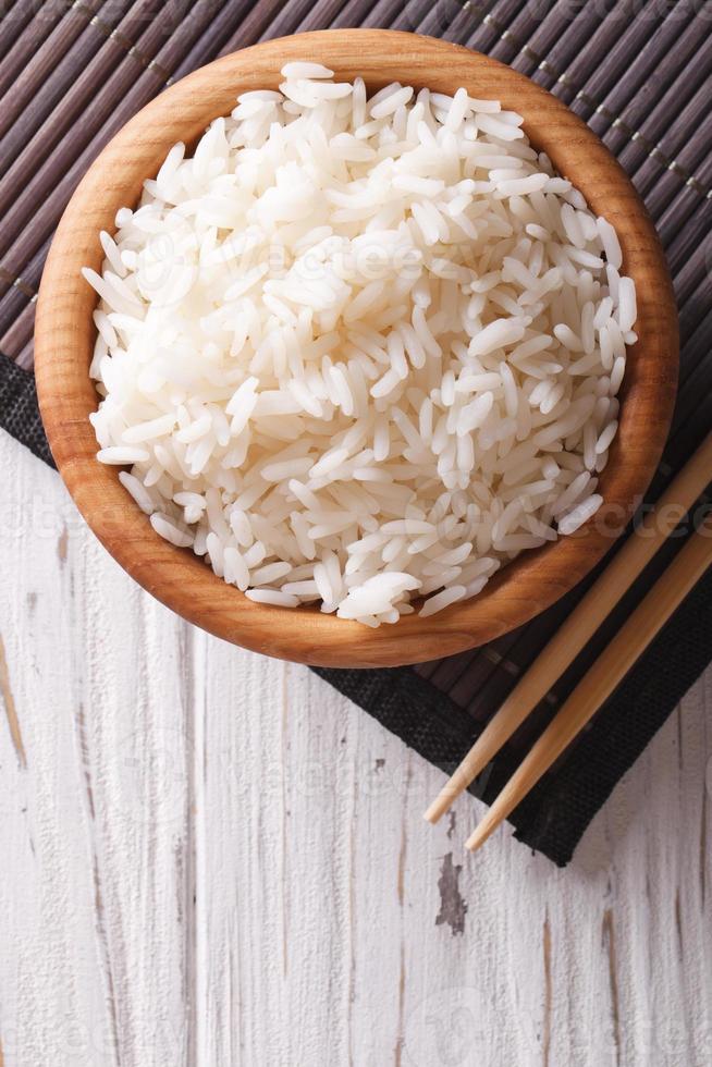Reis in einer hölzernen Schüssel und Essstäbchen vertikale Draufsicht foto