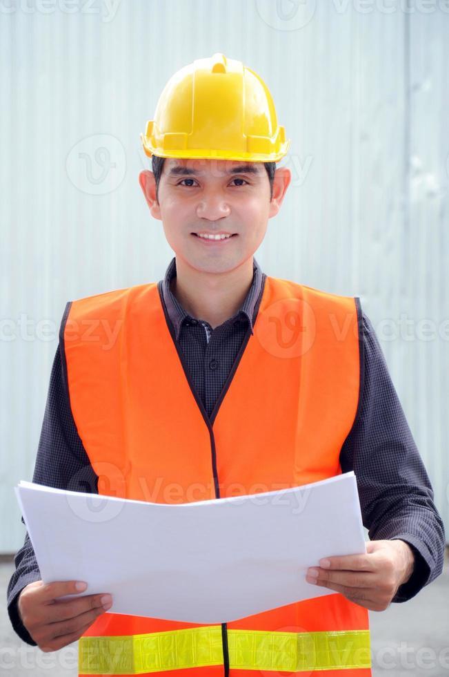 asiatischer Ingenieur oder Vorarbeiter mit Sicherheitsweste und Schutzhelm foto