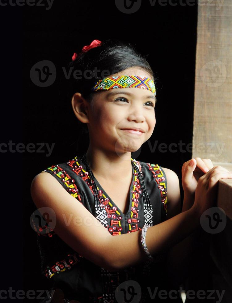 Kadazandusun junges Mädchen in traditioneller Tracht, die am Fenster steht foto