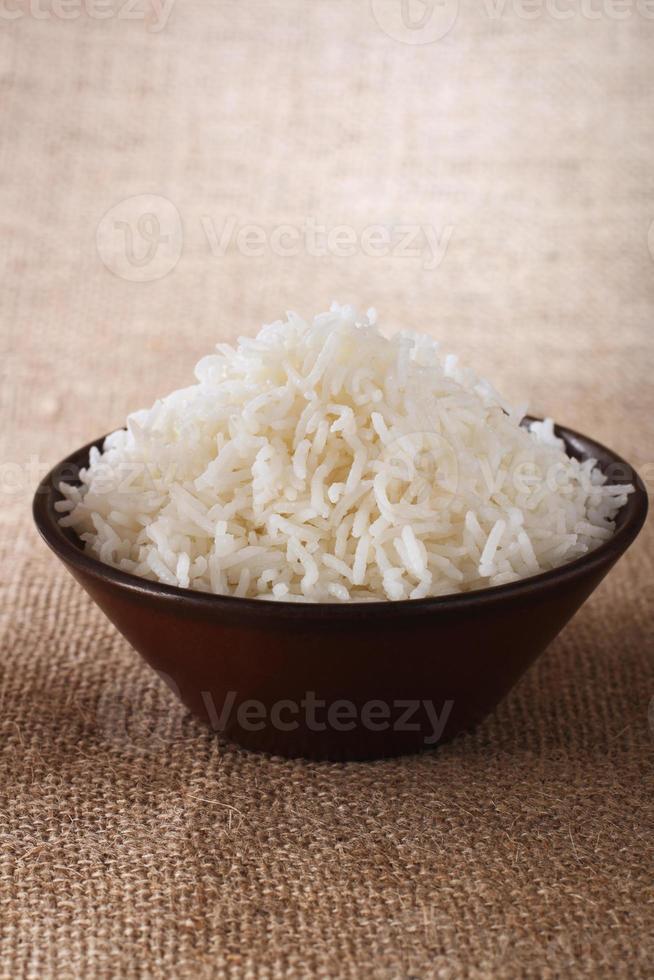 einfache weiße Reisschale auf braunem rustikalem Hintergrund foto