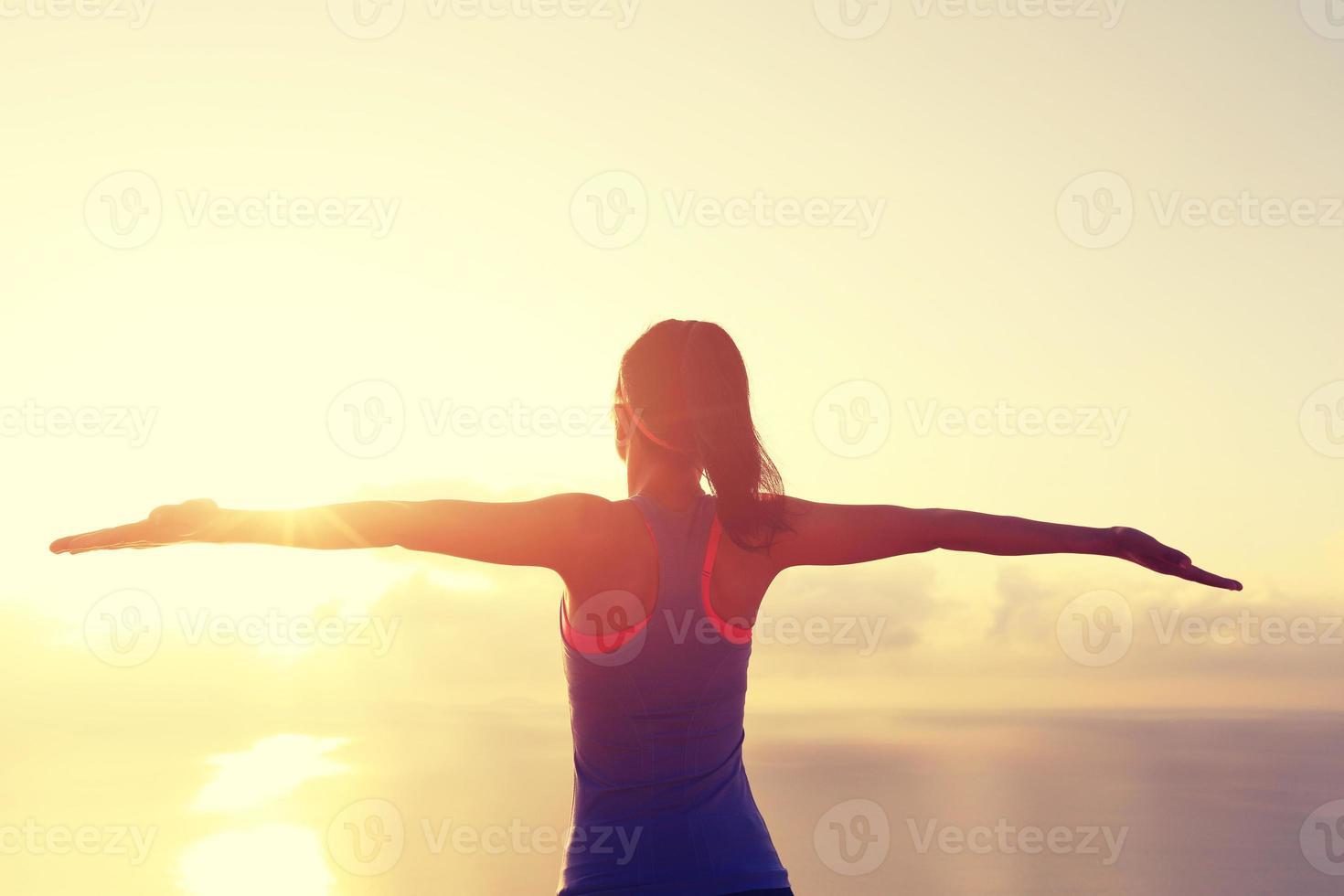 Jubelnde junge Fitnessfrau bei Sonnenaufgang am Meer foto