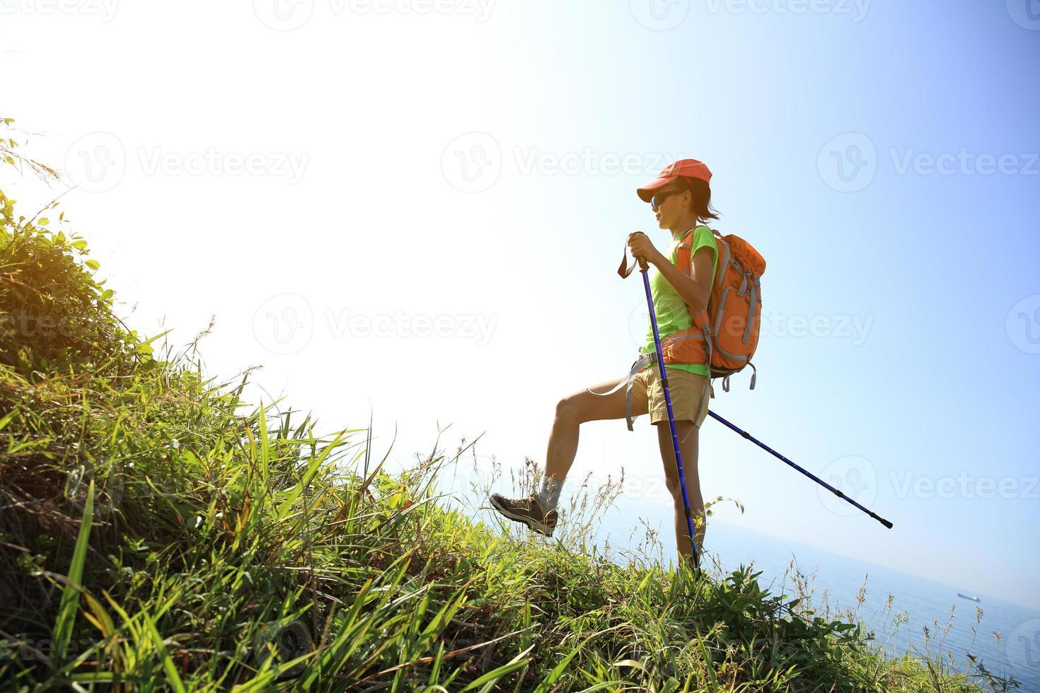 junge Frau, die auf Bergpfad am Meer wandert foto