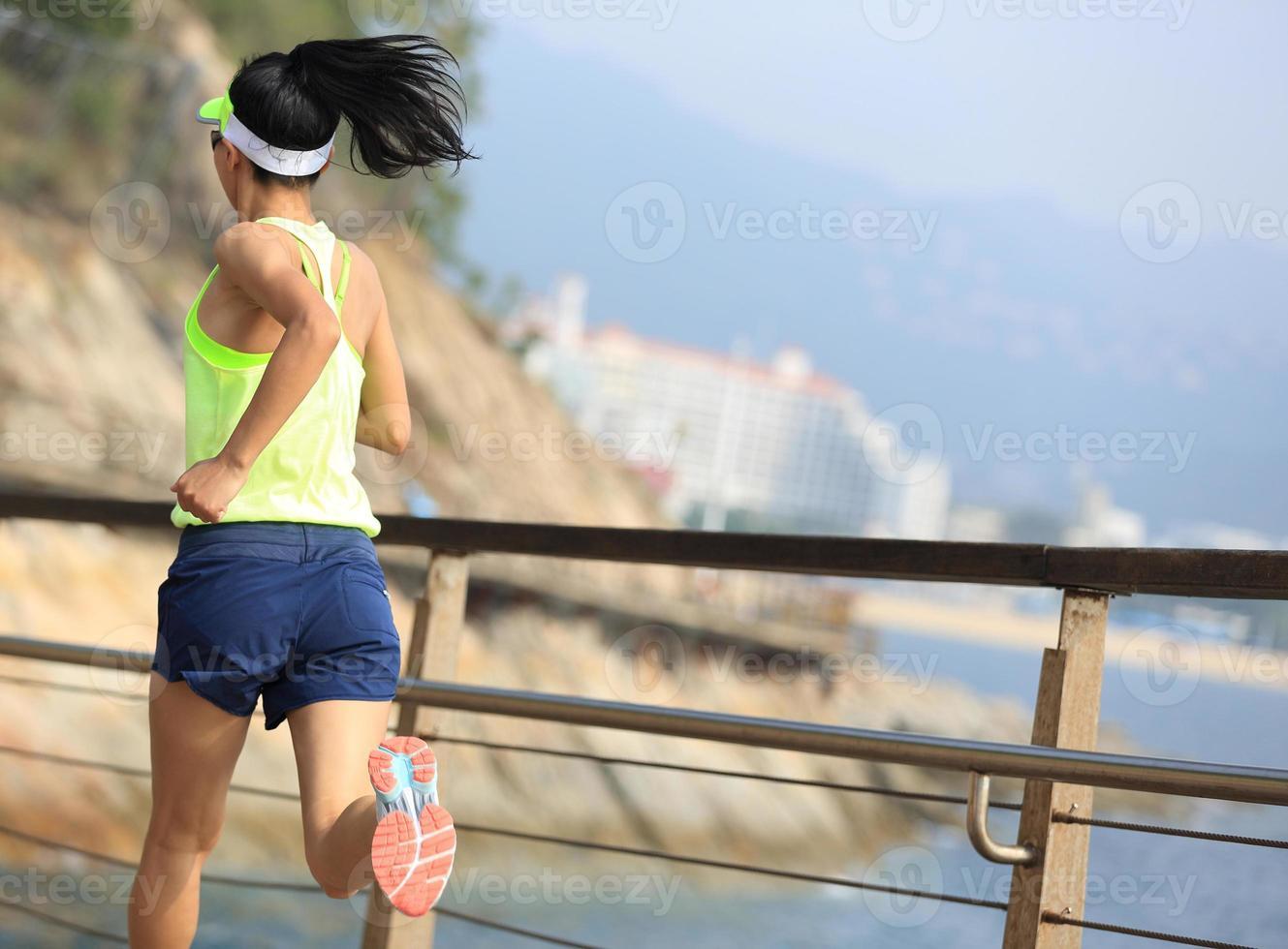 Fitness-Sportfrau, die auf hölzernem Promenadenmeer läuft foto
