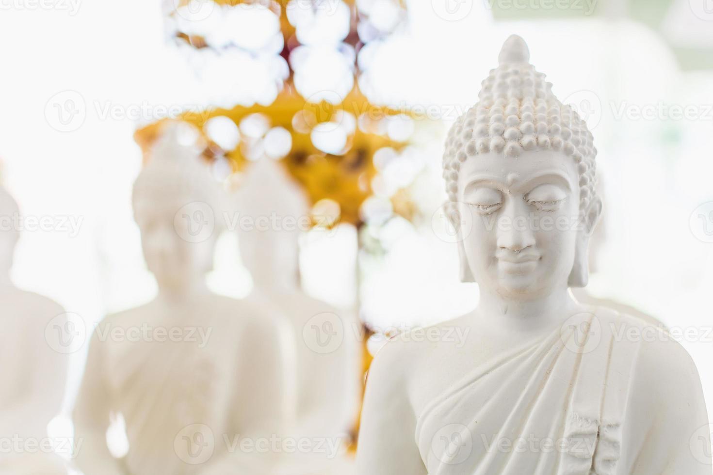 weiße Buddha-Figur im Bokeh. foto