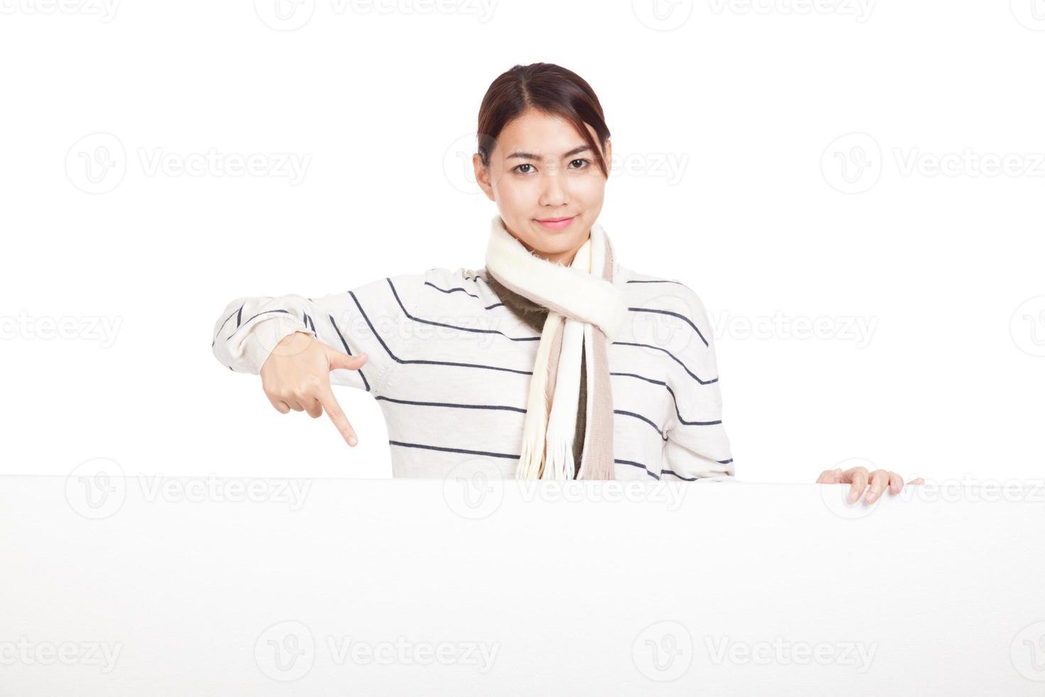 schönes asiatisches Mädchen mit Schal zeigen auf leeres Zeichen foto