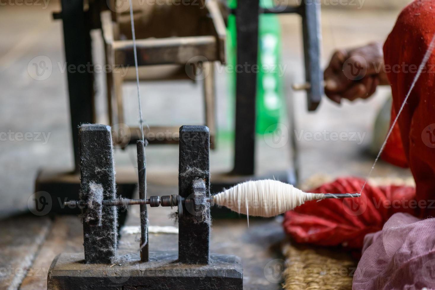 nepalesische Frau, die Baumwolle spinnt foto