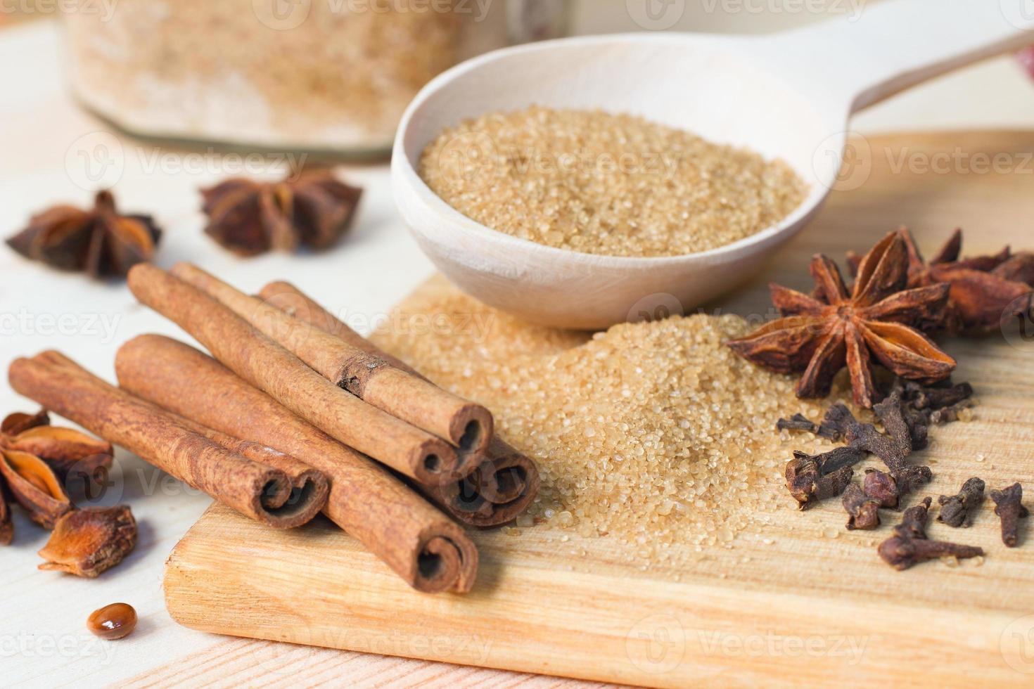 brauner Zucker, Zimtstangen, Sternanis und Nelken foto