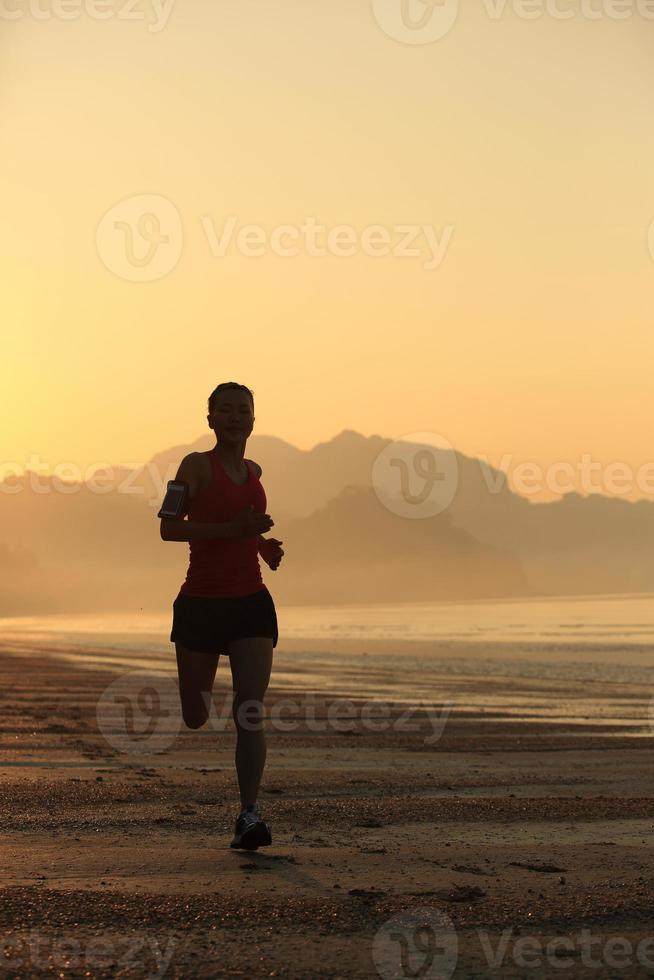 junge Frau läuft am Sonnenaufgang Strand foto