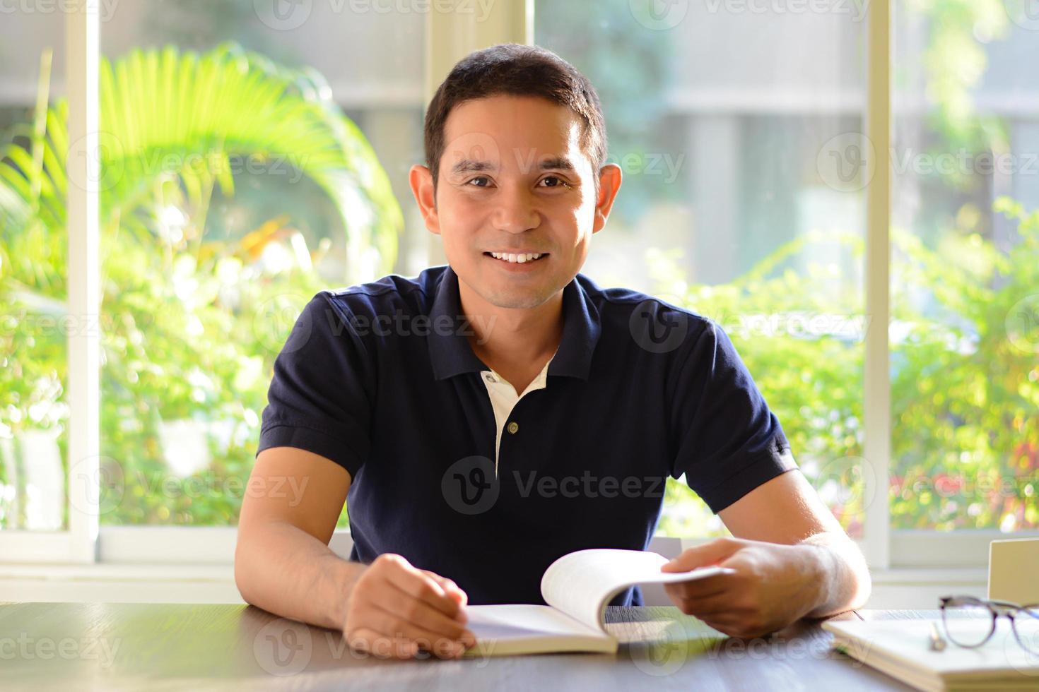 lächelnder Mann mit geöffnetem Buch auf dem Tisch foto
