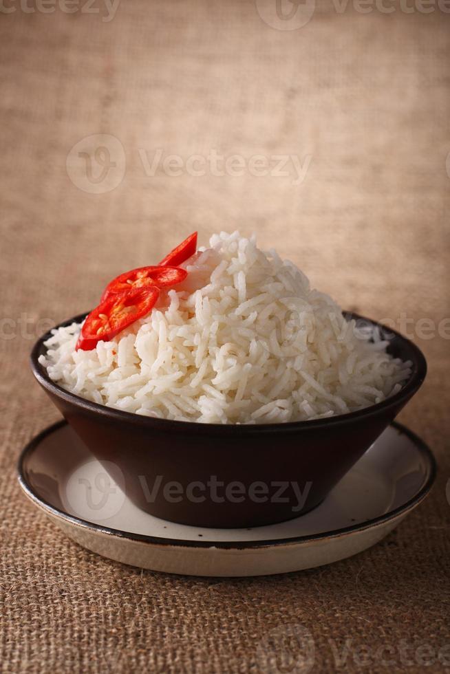 Reisschüssel mit frischen Chilischoten auf braunem rustikalem Hintergrund, foto