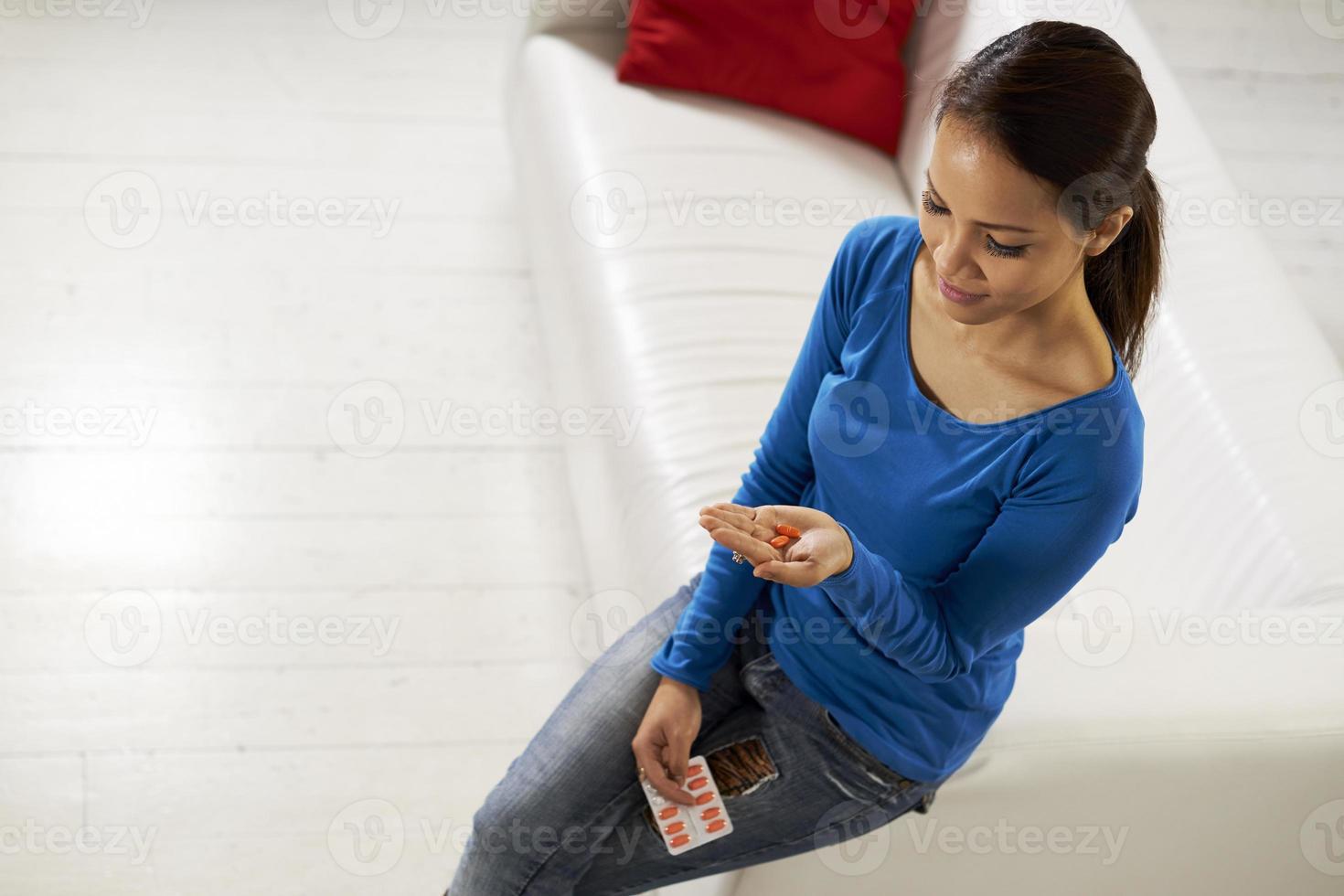 asiatische Frau, die Pillen und Medizin in der Hand hält foto