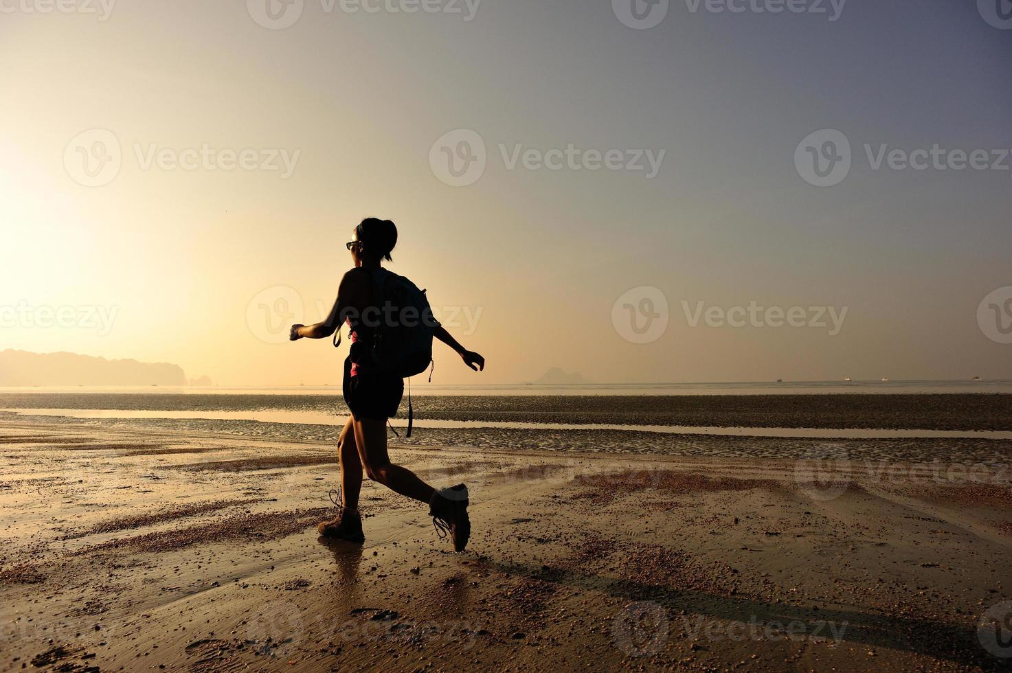 junge Frau, die am Sonnenaufgangstrand wandert foto